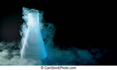 Flask with liquid nitrogen on black background. Concept of...