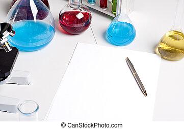 flasks, pen, blank paper, workplace