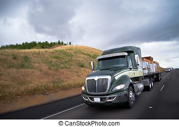 Flat bed semi truck transporting lumber cargo on California...