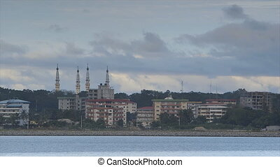 Wide still, late evening shot, close to shoreline, stone protected bank, serene light-blue water, painted flat buildings, white lamp posts along ocean road, thick trees, grand mosque's four large tall, minarets pointing cloudy sky, Conakry
