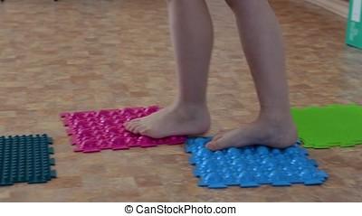 Flat feet correction exercise - child walking over spiked...