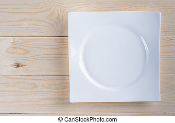 Flat lay above empty white plate on the wooden boards table background