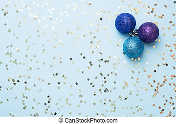 Flat lay background for celebration Christmas and New Year. Balls are purple and turquoise with gold ribbons bows and confetti stars on a blue background. top view copy space.