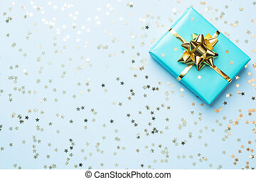 Flat lay background for celebration Christmas and New Year. Gift box turquoise with gold ribbons bows and confetti stars on a blue background. top view copy space.