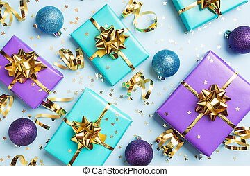 Flat lay background for celebration Christmas and New Year. Gift boxes are purple and turquoise with gold ribbons bows and confetti stars on a blue background. top view