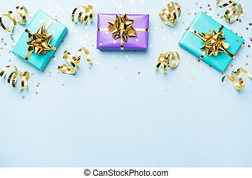 Flat lay background for celebration Christmas and New Year. Gift boxes are purple and turquoise with gold ribbons bows and confetti stars on a blue background. top view copy space.