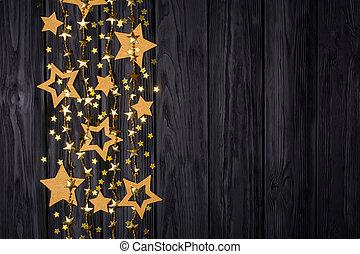Flat lay border of big and small stars of confetti. Festive decor on a black