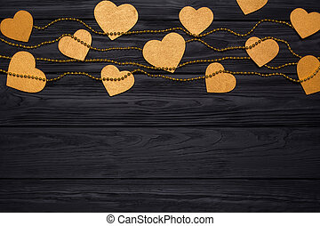 Flat lay border of golden hearts and beads. Festive decor on a black wooden