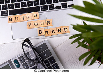 Flat lay build your brand slogan on a tablet pc touchpad.