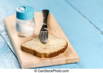 Flat lay butter spread on bread with knife and saltshaker...