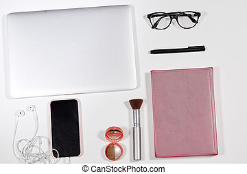 flat lay composition of notebook, diary, pen, glasses, phone, earphones, cosmetics