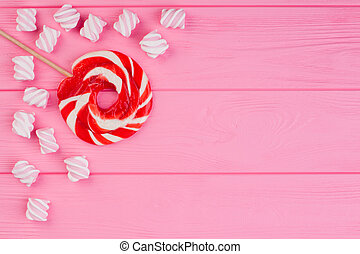 Flat lay composition with candies on pink background.