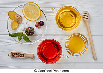 Flat lay composition with tea and honey on wooden background.