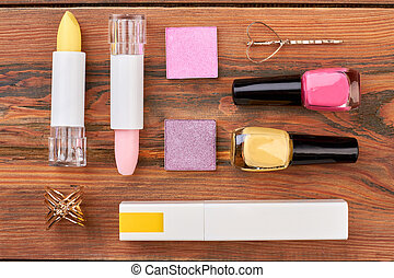 Flat lay cosmetics on brown wooden background.