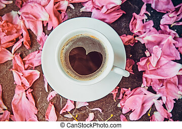 Flat lay cup of coffee with heart shape pattern surrounded with light pink peony flower petals on black stone background. Valentines day, good morning concept. Top view, close up.