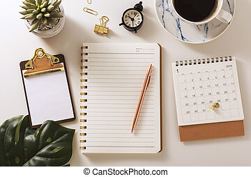 Flat lay desk with notebook, coffee, calendar and green leaf