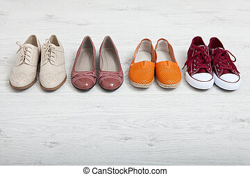 Flat lay fashion set: colored slippers shoes on white wooden background. Top view.