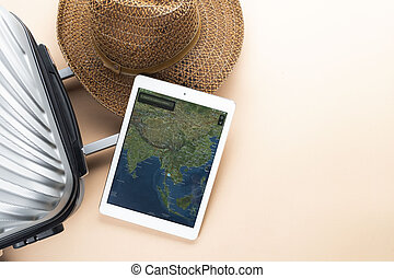 Flat lay grey suitcase with brown hat and map on gadget on pastel background. travel concept - Image