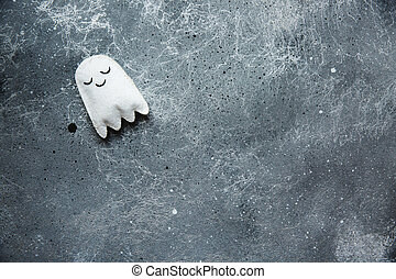 Flat lay Halloween background with decorative ghost on a grey backdrop. Copy space for text