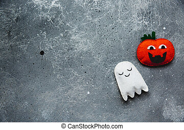 Flat lay Halloween background with decorative pumpkin and ghost on a grey backdrop. Copy space for text