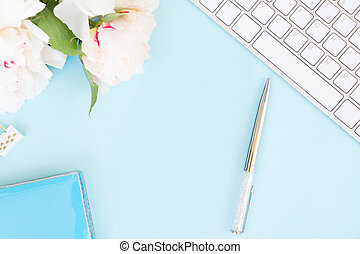 Flat lay home office workspace frame with white modern keyboard and peony flowers, copy space on blue background