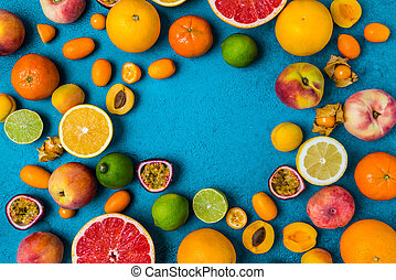 Flat lay layout of summer and citrus fruits on blue background