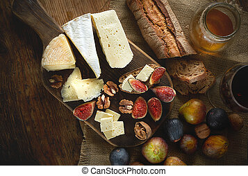 Assortment of cheeses, glass red wine, figs, honey, nuts and bread on wooden table