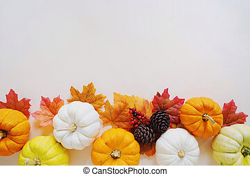 Flat lay of autumn harvest concept, pumpkins and autumn leaves on yellow background with copy space