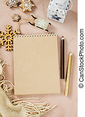 Flat lay of blank brown notebook with Christmas decoration and plaid.