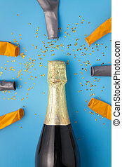 Flat lay of celebration, Champagne bottle and balloon on blue background with glitter