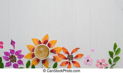 Flat lay of coffee cup with flower petals, leaves on white plank background
