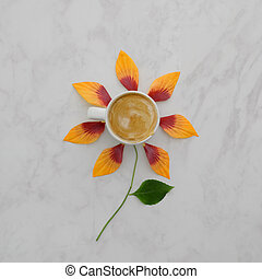 Flat lay of coffee cup with orange flower petals, leaves on marble background