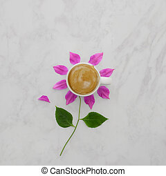 Flat lay of coffee cup with pink flower petals, leaves on marble background
