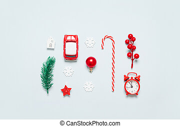 Flat lay of decor frame with Christmas tree branch, clock, twig with berries, toy car, candy cane on a blue background