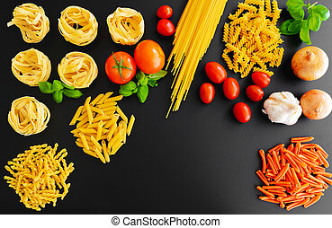 different uncooked italian pasta noodles on dark background with basil leaves, fresh tomatoes and onions