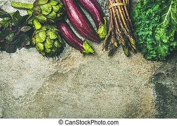 Flat-lay of green and purple fresh vegetables over concrete background, top view, copy space. Local produce for healthy cooking. Eggplans, beans, kale, asparagus, artichoke, basil. Clean eating