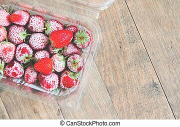Flat lay of frozen strawberries in box on wooden background, Top view