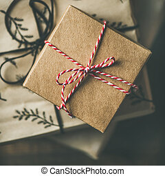 Preparing for Christmas or New Year holiday. Flat-lay of gift boxes, rope, scissors over rustic wooden table background, top view, square crop