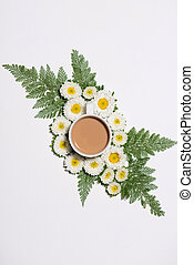 Flat lay of green leaves and flowers pattern with cup of coffee on white background