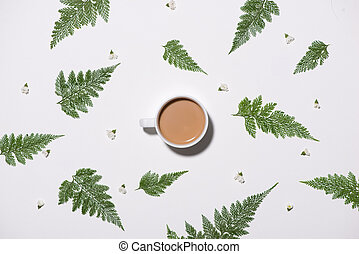 Flat lay of green leaves pattern with cup of coffee on white background