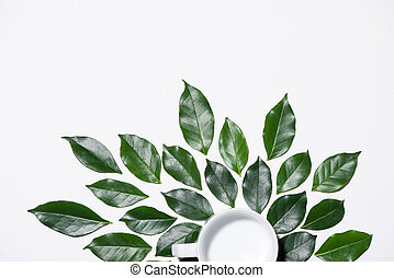 Flat lay of green leaves pattern with cup of milk on white background