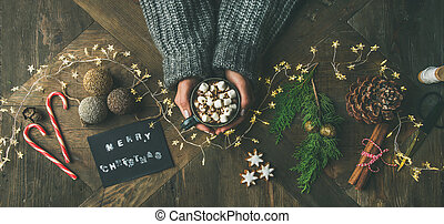 Flat-lay of greeting card, garland, woman's hands holding...