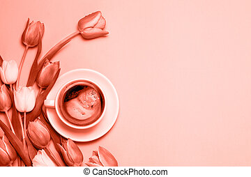 Flat lay of minimalistic picture of cup of coffee and tulips colored in living coral.