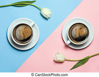 Flat lay of minimalistic picture of two cups of coffee and tulips on pink and yellow background.