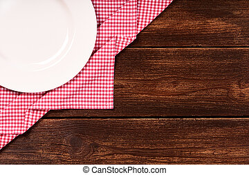 Flat lay of old wooden background with red checkered dishcloth and round white plate