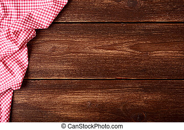 Flat lay of old wooden background with red checkered dishcloth