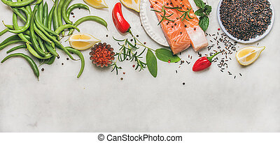 Flat-lay of raw salmon fillet steaks with vegetables, greens...