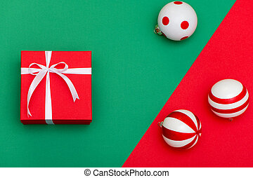 Flat lay of red gift box with white ribbon and Christmas toys on green and red background.