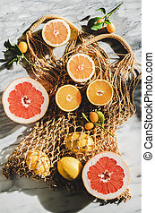 Flat-lay of summer net bag with fresh citrus fruits, close-...