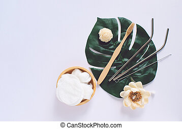 Flat lay of sustainable products, wooden spoon, stainless straw and natural cotton on green plant and white background with copy space, eco friendly and zero waste concept